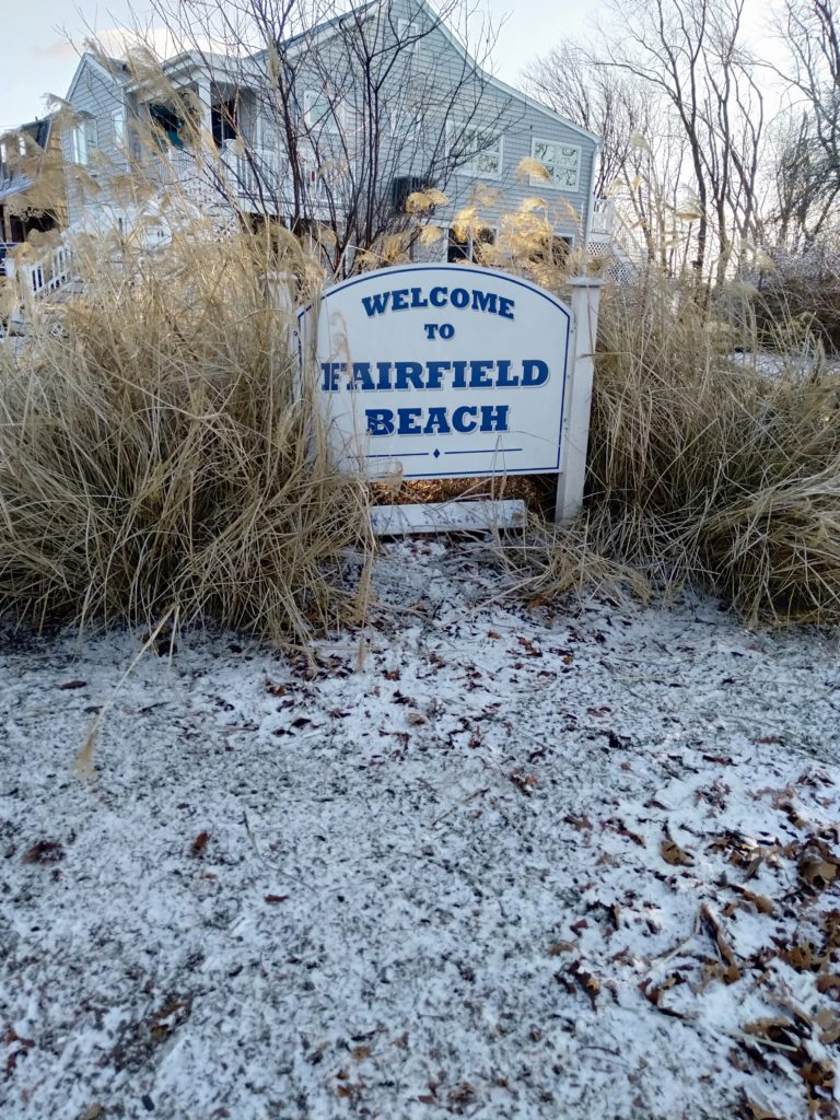 Welcome to Fairfield beach sign with snow around it.